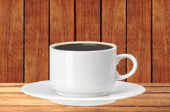 White cup of coffee on wooden table over wooden planks Royalty Free Stock Photo
