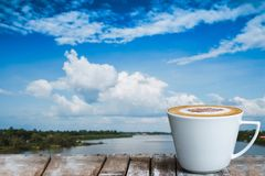 A white cup of coffee on the wooden table by the river royalty free stock photography