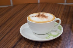 White cup containing hot cappuccino coffee on table Royalty Free Stock Image