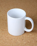 White cup on corkboard background. Stock Photography