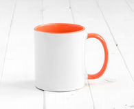 White cup with dark orange inside on a table Royalty Free Stock Image
