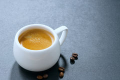 White cup of espresso and coffee beans on a dark background Stock Images
