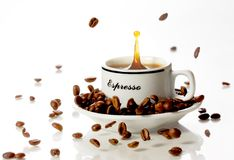 Coffee scplash. A white cup filled with coffee with a splash of beans. On a white background Royalty Free Stock Image