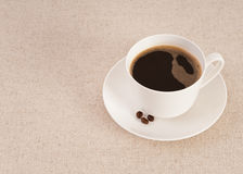 White cup filled with fresh black coffee. White coffee cup, black coffee and coffee beans on canvas Stock Photo