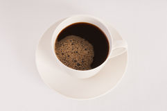 White cup filled with hot black coffee. White cup filled with black coffee on white background Royalty Free Stock Photography
