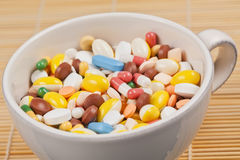 White cup filled with medicine pills Stock Images