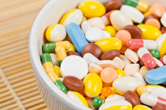 White cup filled with medicine pills Stock Photos