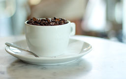 White cup filled with roasted coffee beans. All on a marble table Royalty Free Stock Image