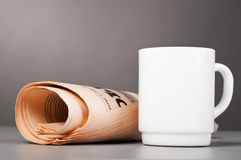 White cup and folded newspaper Royalty Free Stock Image