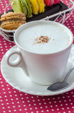 White cup of  fresh cappuccino and sweet macaroons for morning c Royalty Free Stock Images