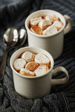 White cup of fresh hot cocoa or hot chocolate with marshmallows on grey knitted background Royalty Free Stock Photos