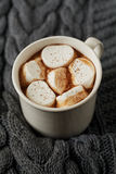 White cup of fresh hot cocoa or hot chocolate with marshmallows on grey knitted background Royalty Free Stock Image