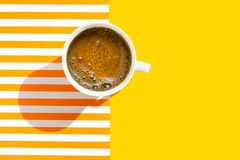 White cup of freshly brewed coffee with foamy crema on duotone yellow white striped background. Top view. Morning breakfast energy. Fashion business concept stock photos
