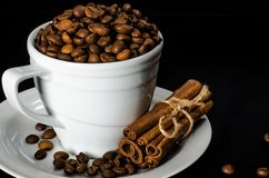 A white cup full of coffee beans stands on a white saucer, which stands on a black background royalty free stock image