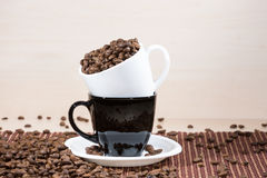White cup full of roasted coffee beans standing on a black on white plate standing on tablemat. Stock Photography