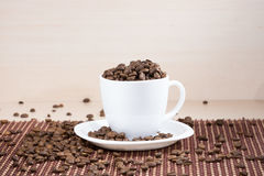 White cup full of roasted coffee beans standing on a white plate on tablemat. Stock Photo