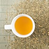 White cup of green tea. Over tea leaves scattered over bamboo mat as a background Stock Photos
