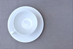 White cup on a grey napkin background texture Royalty Free Stock Photos