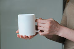 White cup in hand of a girl stock image