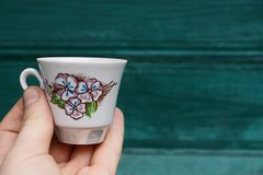 White cup in hand on a green background. Hand holding a white cup with a pattern Royalty Free Stock Photos