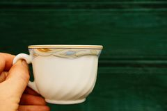 White cup in hand on a green background. Hand holding a white cup with a pattern Stock Photos