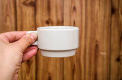 White cup in hand on wooden background royalty free stock photos