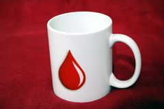 White cup having blood drop mark inspiring to donate blood royalty free stock image