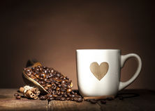 White cup with heart and coffee beans Royalty Free Stock Image