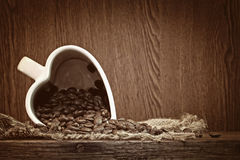 White cup heart shape with coffee beans Stock Photos