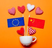 White cup and heart shapes with Europe Union and CHina flags. On orange background royalty free stock images