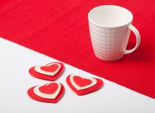 White cup with hearts on a red napkin Stock Images