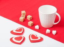 White cup with hearts and sugar on a red napkin Royalty Free Stock Images
