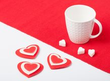 White cup with hearts and sugar on a red napkin Royalty Free Stock Photo