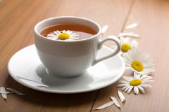 White cup of herbal tea and camomile flowers Royalty Free Stock Images