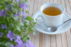 Cup of tea in saucer Flowers Bamboo tabletop Stock Photo