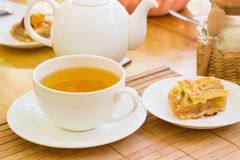 Herbal tea and a piece of cake on a saucer Royalty Free Stock Photo