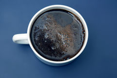 White Cup of hot black coffee on blue background. The white Cup of hot black coffee on blue background Stock Photography