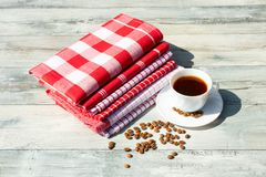 White  cup of hot black coffee with roasted coffee beans togethe. R with a Stack of red white checkered and striped linen tableclothes on rustic bright wooden Royalty Free Stock Image