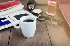 White cup hot black coffee on wood table with working women thin Royalty Free Stock Photography