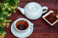 White cup of hot black tea, teapot and honey of linden tree Stock Photo