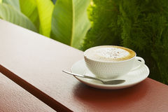 White cup of hot cappuccino coffee in terrace Stock Photos
