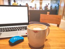 A white cup hot capuccino with lipstick smudge, a computer labtop and blue mouse on brown wooden table infront counter bar stock images