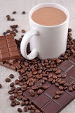 White cup of hot chocolate on coffee beans and chocolate backgro Royalty Free Stock Images