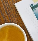 White cup of hot coffee. And a book on wood table Royalty Free Stock Photo