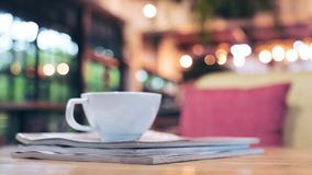 A white cup of hot coffee above the books on wooden table with blur background in cafe. Closeup image of a white cup of hot coffee above the books on wooden royalty free stock photo