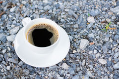 White cup of hot coffee on gray stone ground nature background. White cup of hot coffee with white plate on gray stone ground nature background. shallow focus Royalty Free Stock Images