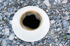 White cup of hot coffee on gray stone ground nature background. White cup of hot coffee with white plate on gray stone ground nature background. shallow focus Stock Images