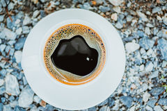 White cup of hot coffee on gray stone ground nature background. White cup of hot coffee with white plate on gray stone ground nature background in vintage tone Stock Photos