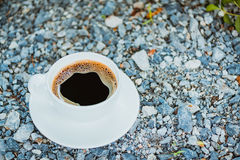 White cup of hot coffee on gray stone ground nature background. White cup of hot coffee with white plate on gray stone ground nature background in vintage tone Royalty Free Stock Photography