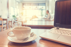 White cup of hot coffee with laptop on wooden table in cafe. Royalty Free Stock Photo